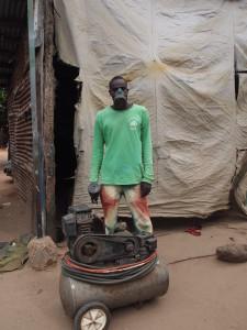 Autospuiter Muhammed Jammeh maakt Team Ousman compleet. De compressor is de trots van het bedrijf, en achter Muhammed zie je de 'spuitcabine'