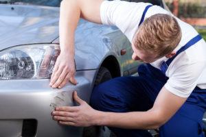 Een monteur bekijkt de schade aan een auto