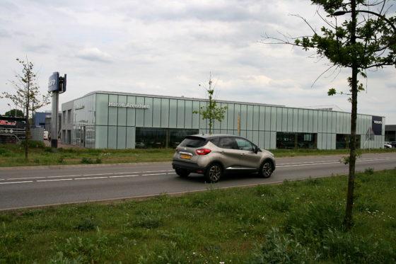 Vanaf de doorgaande weg is te zien dat de glazen gevel deels melkglas en deels helder glas heeft, helemaal volgens de Volvo-standaard. Straks zullen op het gras schapen lopen.