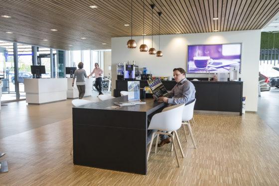De klant heeft een comfortabele plaats gevonden aan de koffietafel. Rechts is de showroom en links de werkplaats. De klanten mogen ook in de werkplaats naar hun auto lopen.