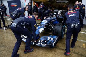 Nee, je mag een F1 niet optillen aan de frontspoiler. Ook het doorbuigen van spoilers onder rijbelasting wordt meegenomen in aerodynamische berekeningen, om daar voordeel uit te halen. (foto Red Bull)