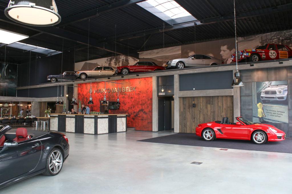 De grootste blikvanger in de showroom zijn de vijf auto's op de vide. Achter elke auto hangt een foto. De auto's en foto's hebben voor Marco een bijzondere betekenis.